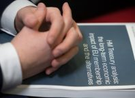 A guests hold a report published by Britains Treasury on the economic impact of Brexit