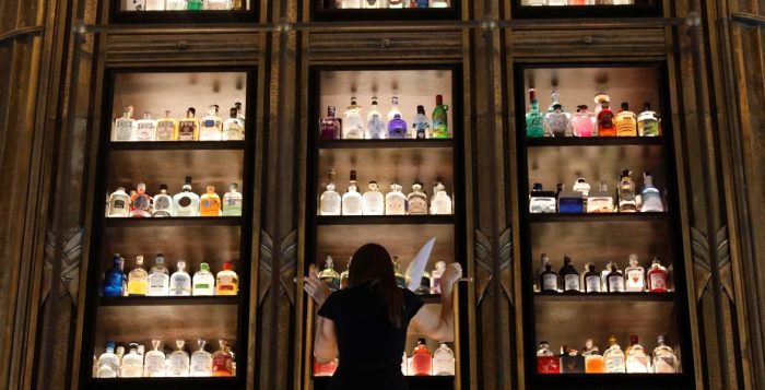 A woman climbs a ladder to reach a bottle from a collection of gin in the gin tower restaurant