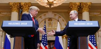 Donald Trump and Russias President Vladimir Putin shake hands during a joint news conference