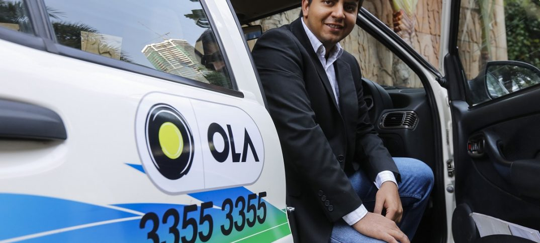 Bhavish Aggarwal, CEO and co-founder of Ola, an app-based cab service provider, poses in front of an Ola cab in Mumbai - Image: REUTERS/Shailesh Andrade