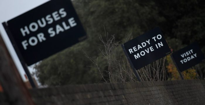 Property sale signs are seen outside of a group of newly built houses in west London. REUTERS/Toby Melville