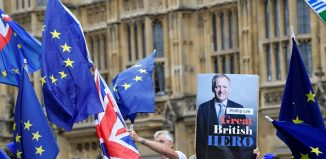Anti-Brexit demonstrators wave Union and EU flags and hold up a placard mentioning Phillip Lee, a minister who resigned today after disagreeing with the government's handling of Brexit. REUTERS/Toby Melville